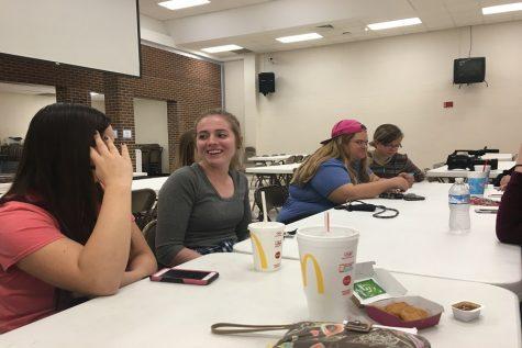 Seniors Sierra Eichman, Veronika Fuller, Rachelle Lumpkins and Alyana Arnhold wait for instructions in the cafeteria, where the tallying for Kids Vote Kansas took place.