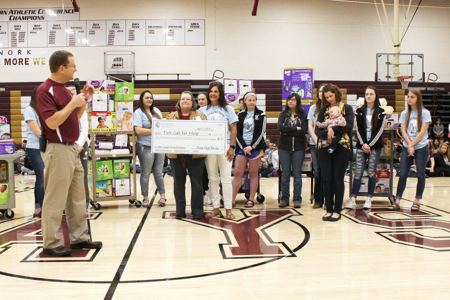 Instructor Sue Ann Tebo and her family studies students are introduced by principal Martin Straub. The class presented Ellis County First Call for Help with a contribution of over 7,000 diapers.