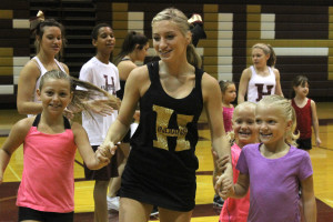 Cheerleaders work with children at Youth Cheer Camp