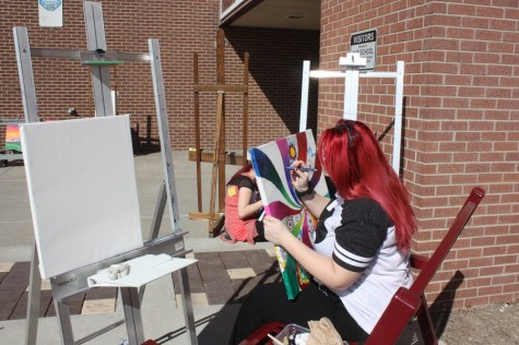 Art students paint outside during nice weather