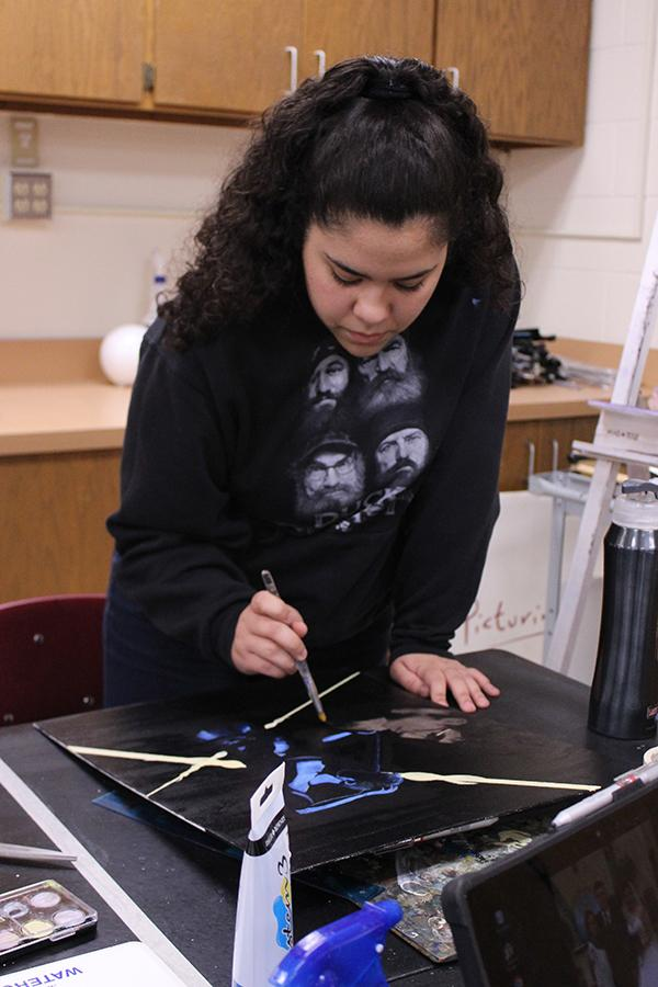 Sophomore Iris Garibay works on a painting in during class.