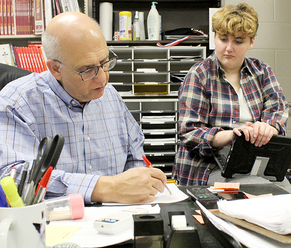 Journalism instructor Bill Gasper helps newspaper student Elizabeth Lee with story corrections.