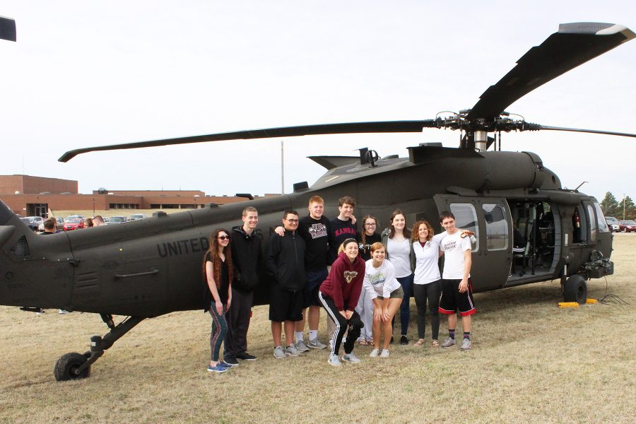 Instructor Abby Maska stands in front of one of the helicopters with her senior AP government class.