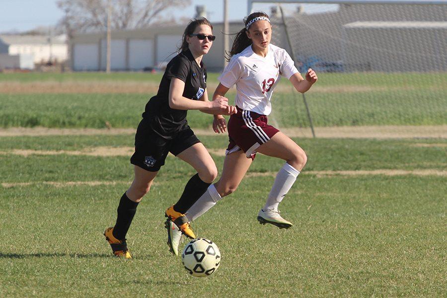 Sophomore+Kallie+Leiker+runs+alongside+an+opposing+team+member+during+a+recent+home+game.