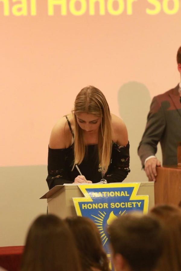 Junior Myranda Berner signs her name in the induction book during the ceremony. Photo taken by Lindsey  Pfannenstiel.