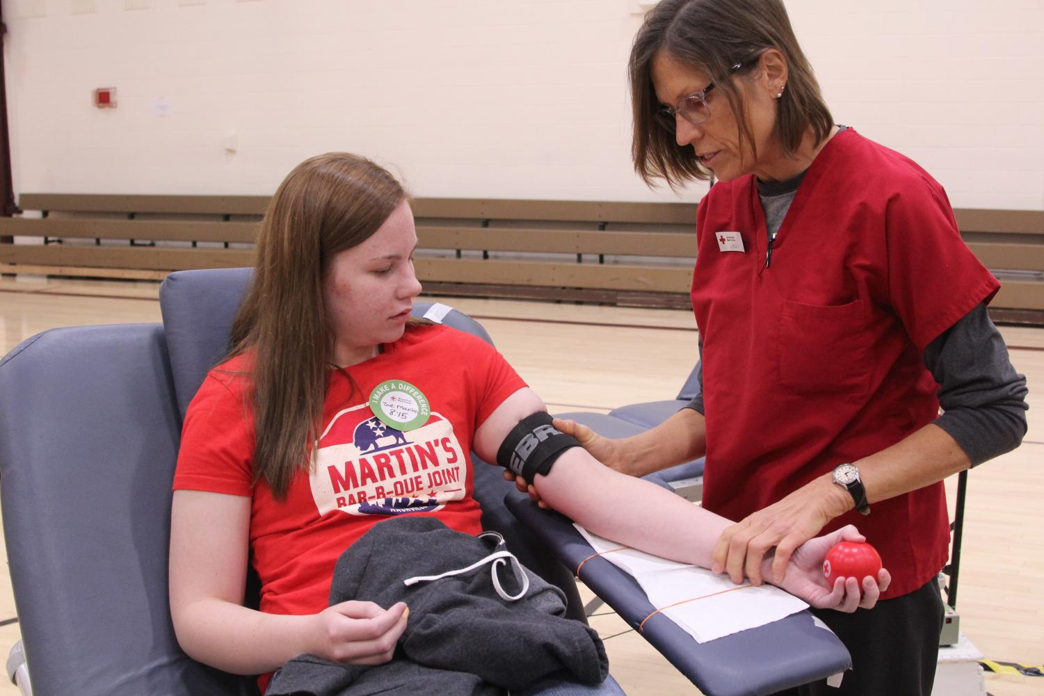 Junior Zoe C. Martin squeezes the ball as the nurse explains the procedure on Nov. 1. Martin was one of 55 people who were able to donate.