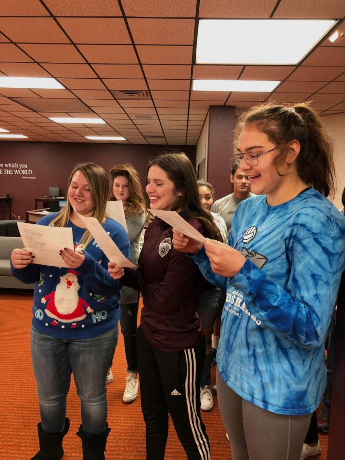 Juniors+Lindsey+Pfannenstiel%2C+Hannah+McGuire+and+Jaysa+Wichers+carol+in+the+library+during+G2.+This+is+their+second+year+caroling.