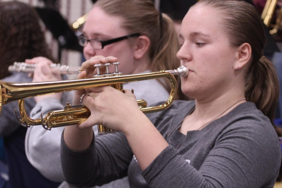 Sophomore Chloe Fitzhugh plays her trumpet during a break in the Basketball game.
