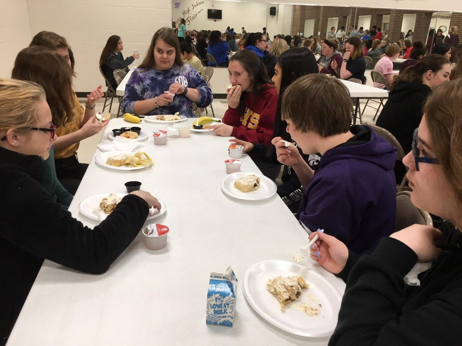 Students eat their cinnamon rolls at Breakfast of Champions.  Breakfast of Champions was held March 28 during first hour for students who earned a 3.3 GPA or above during the third quarter.