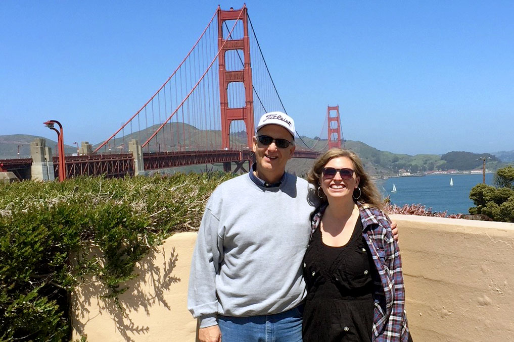 Hays High alumni Delphine Burns poses with journalism instructor Bill Gasper in front of the Golden Gate Bridge.